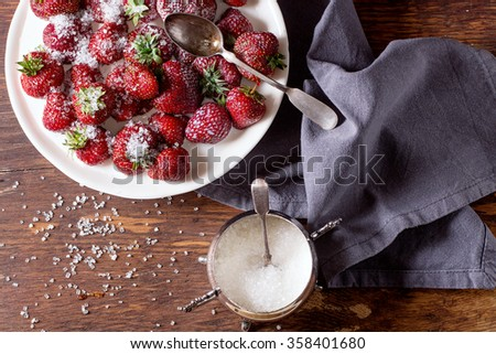 White plate with fresh ripe garden strawberries with sugar, sugar-bowl and spoons on wooden table. Dark rustic style. Top view - stock photo
