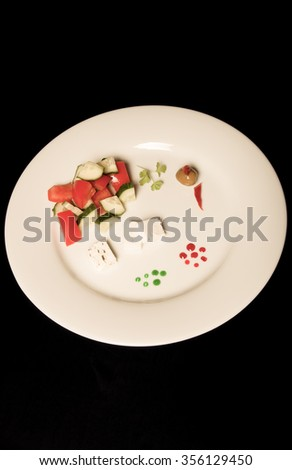White plate with fresh salad on a black table or background. Toned.