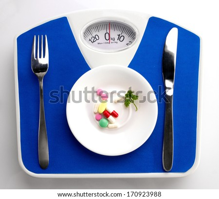 white plate with leaf of parsley and supplement,  spoon and knife on blue scale, top view - stock photo