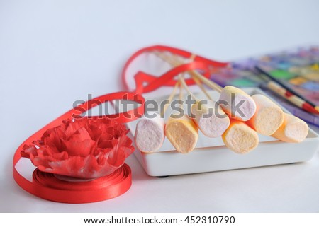 white plate with marshmallows on wooden stick and red ribbon on background further paintbrushes on paint palette and red edible rose bloom on top of ribbon roll
