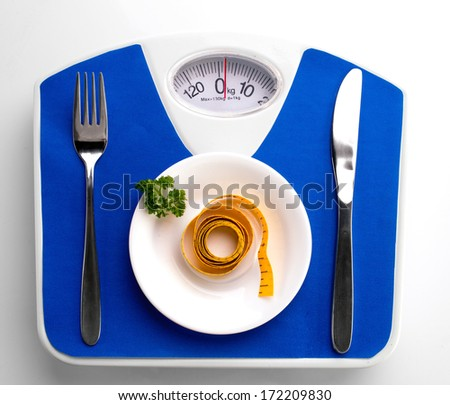 white plate with parsley and measure, spoon and knife on blue scale, on white background  - stock photo