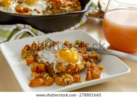 White plate with single fried egg and sweet potato hash with fork, grapefruit juice and whole grain toast