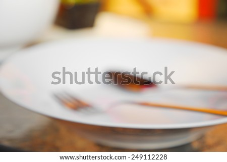 White Plate with Spoon and Fork - Blurred Background - stock photo