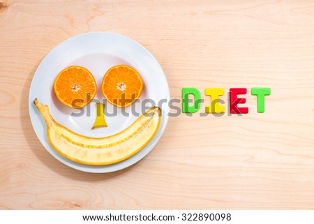 white plate with the word diet of different fruits on a wooden table - stock photo