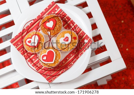 white plate with valentine's day muffins with red and white hearts on a white wooden table