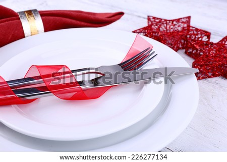 White plates, knife, fork, napkin and Christmas decoration on wooden background - stock photo