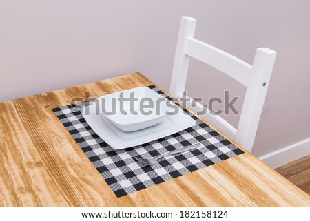White plates on a wooden table - stock photo