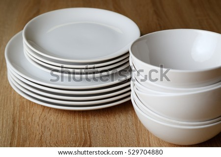 White plates on a wooden table. Close-up.