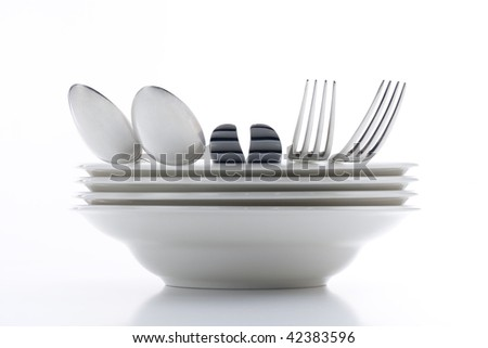 white plates with silverware isolated on white - stock photo