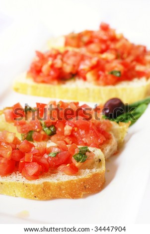 White platter of bruschetta with red tomato and basil