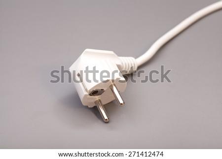 White plug isolated on gray background - stock photo