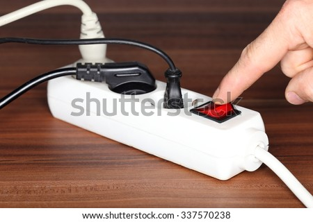 white plug socket on a wooden table - stock photo
