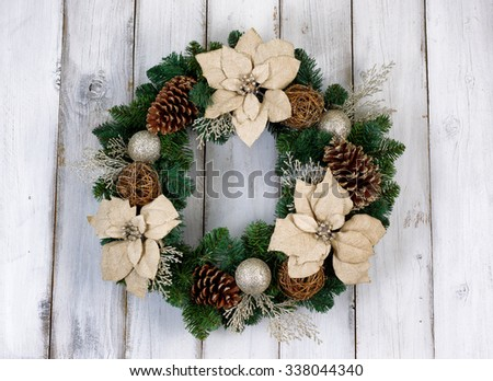 White Poinsettia flower and pine cone Christmas wreath on rustic white wood.