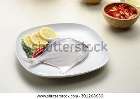 white pomfret fresh fish on white plate with lemon - stock photo