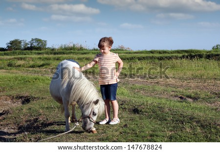 white pony horse and little girl on field