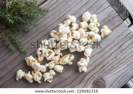 White popcorn and green thyme, on wooden background - stock photo