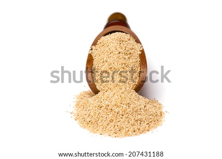 White poppy seeds in wooden scoop on white background