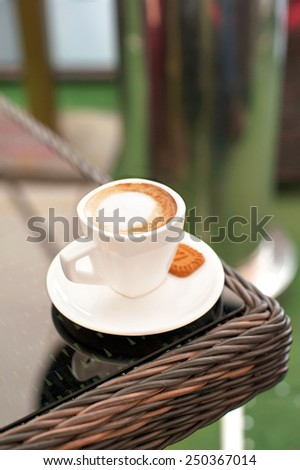 White porcelain cup of black coffee with whipped milk on rattan table in summer cafe. Outdoors closeup. - stock photo