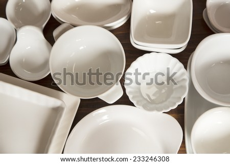 White porcelain dishes and utensils on a wooden background - stock photo