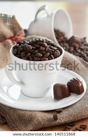 White porcelain mug filled with coffee grain and chocolates