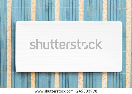 White porcelain plate on a blue straw background - stock photo
