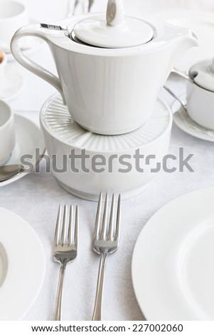 white porcelain tea set: teapot, saucer, cup - stock photo