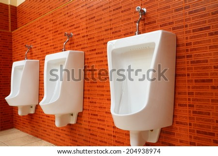 White porcelain urinals in gents toilets - stock photo