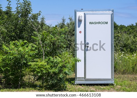 White Portable Washroom Surrounded By Trees In A Camp Ground