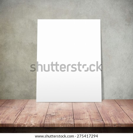 White poster on a wooden table with concrete wall background