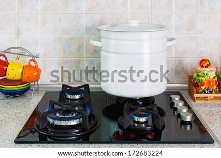 white pot on a gas stove delivered in the kitchen - stock photo