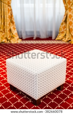 White pouffe in the room with vintage red carpet and classic yellow drapes - stock photo