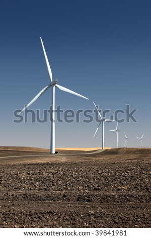 White power generating windmills under blue sky and recently tilled agricultural land.