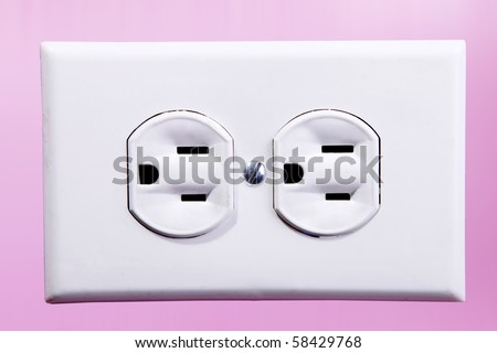 White power plug in a pink wall - stock photo