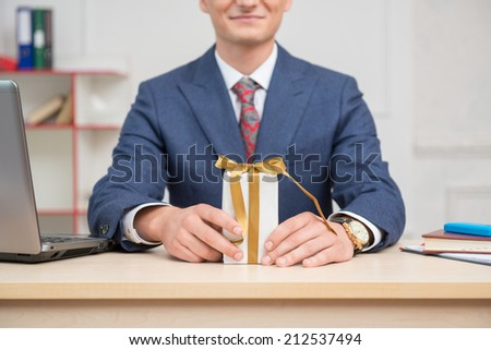 White present box with gold ribbons standing on the table in hands with a clock of young businessman in office surrounded by computer,notebook and mobilephone - stock photo