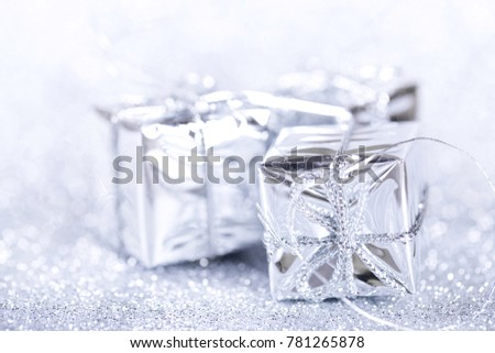 White present boxes on shiny silver background.  Christmas and New Year decoration