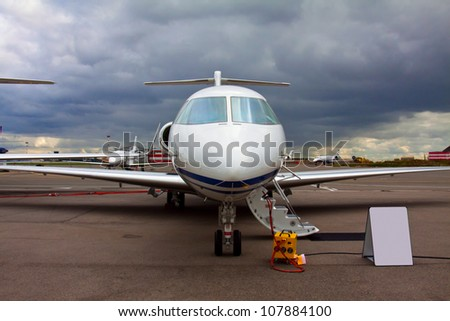 white private jet and open ladder, at the airport on a background cloudy sky - stock photo