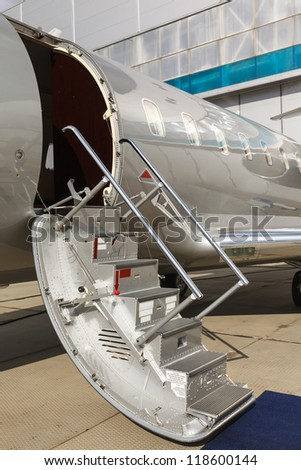 white private jet and open ladder, carpet at the airport  - stock photo