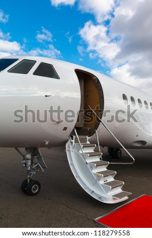 white private jet and open ladder, red carpet at the airport on a background blue sky - stock photo