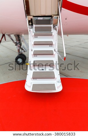 white private jet and open ladder with red carpet at the airport