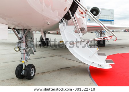 white private jet and open ladder with red carpet at the airport  - stock photo