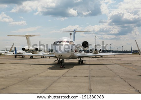 white private jet on the platform airport in the sun in summer - stock photo