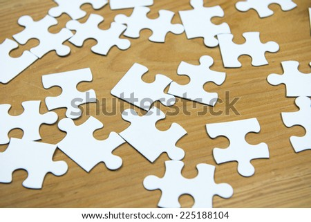 White puzzle on wood background - stock photo