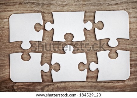 white puzzle pieces on wooden background - stock photo