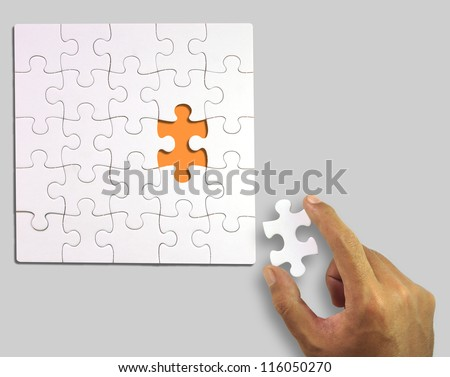 White puzzle with a piece in hand (Clipping Path) - stock photo