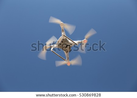 White quadrotor helicopter is flying in sky