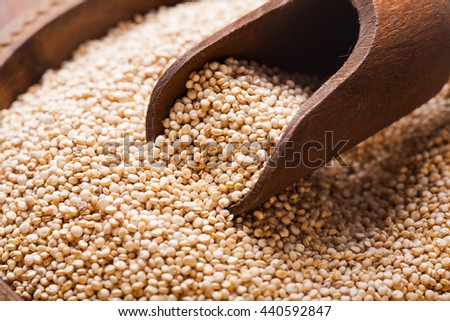 White quinoa seeds on a wooden spoon in a bowl