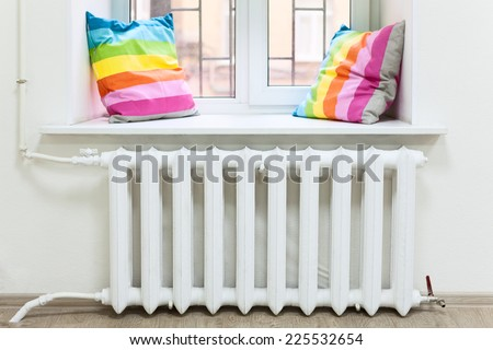 White radiator of central heating is in domestic room under window - stock photo