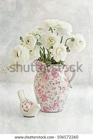 White Ranunculus in a flower vase on a table. soft focus and old paper texture .