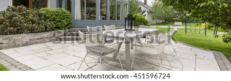 White rattan garden table with set of chairs in a paved backyard of a luxurious villa