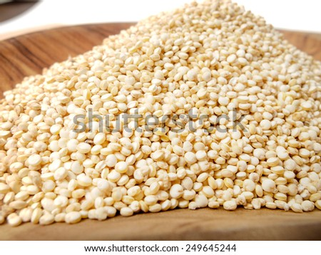 White raw Quinoa seeds in a brown wooden bowl - stock photo